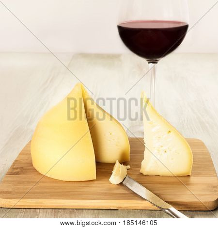 A square photo of tetilla, a traditional Spanish soft cow milk cheese, with a slice cut off, and a glass of red wine, on a wooden board with a place for text, toned image