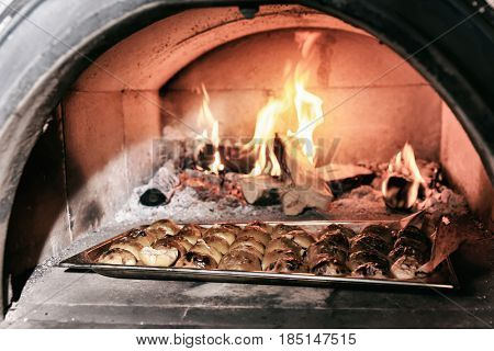 Apple halves being roasted in wood fired oven, professional kitchen of a restaurant, toned image