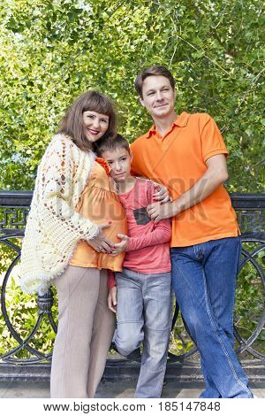 Happy family with pregnant mother in summer embankment