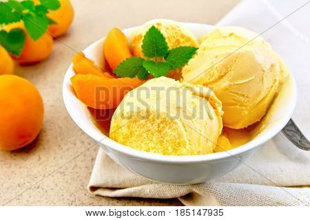 Apricot ice cream in a white bowl with slices of fruit, mint and spoon on a napkin on a granite background table