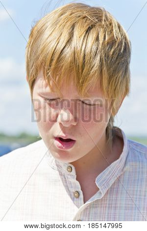 Portrait of squint blond boy in a white shirt near river