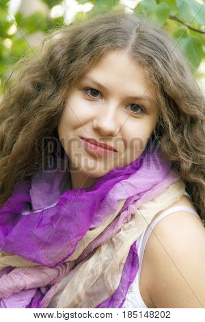 Young beautiful girl with curly hair in purple scarf