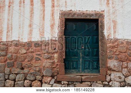 Old ancient grunge door in Peruvian brown house. Closed green door