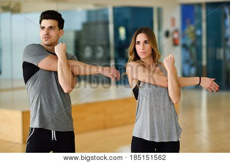 Two People Stretching Their Arms In Gym.