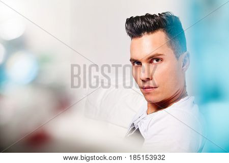 Beautiful model, handsome man portrait. Hairstyle modern look. Close portrait of a young man with stylish hair. Lights, colors, bokeh. Beautiful face and serene expression. Intense look.