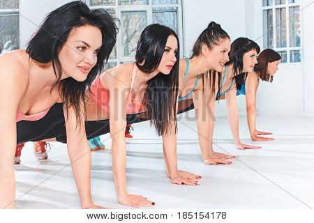 The group of fit young women training in a gym or a fitness center. Healthy and fitness concept