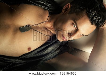 Attractive sexy male, handsome cool man. A beautiful stylish man in glamorous style. Chest discovered with metal necklace. Stylish hair. Relaxed lying.