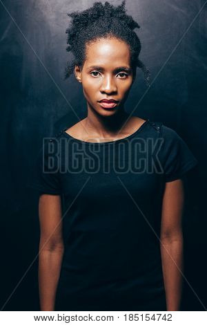 A calm and confident African American woman in a black T-shirt on a dark background looks at the camera. Portrait to the waist. Self-sufficiency, confidence, pride, uniqueness of personality concept
