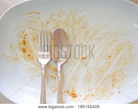 Empty dish with spoon and fork after food on the table
