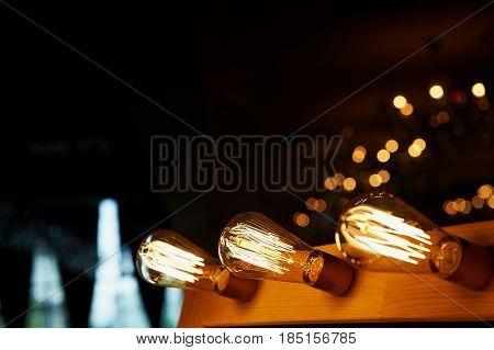Edison light bulb hanging on a long wire. Cozy warm yellow light. Retro