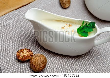 Traditional bechamel sauce and ingridients on tableware