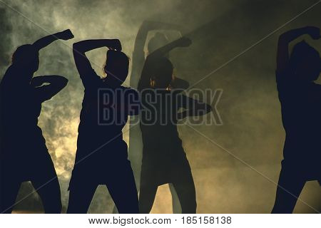 silhouettes of dance crowd in front of bright stage lights