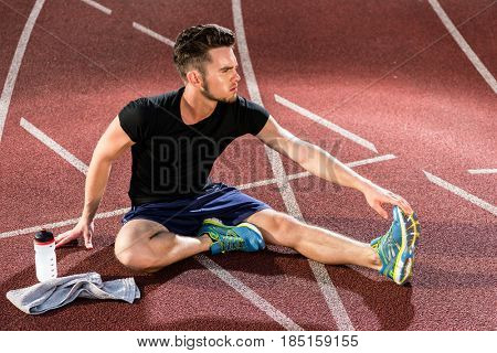 Athlete stretching on racing track before running