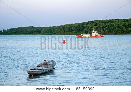 Beautiful river lanscape with small old boat and small barge in background