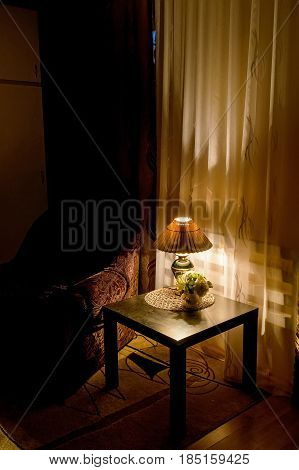 Cozy bedroom interior with armchair and reading lamp and vase with flowers