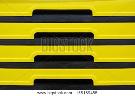 Close up pile of black and yellow plastic boxes