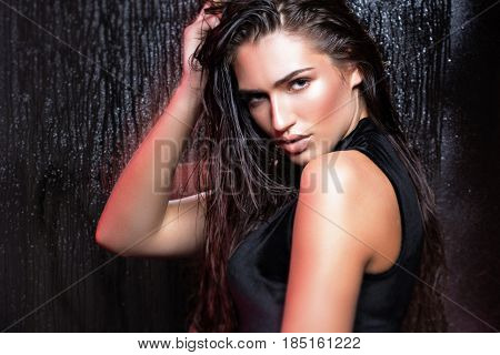 Beauty woman with wet hair and natural makeup, the background of wet glass.