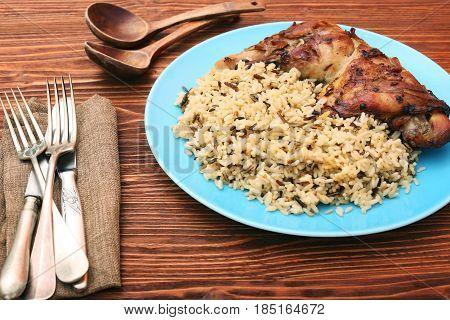 Roasted turkey leg with wild rice on wooden background