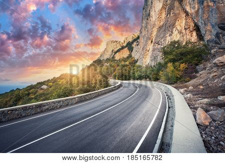 Beautiful asphalt road. Colorful landscape with high rocks, mountain road with a perfect asphalt, trees and amazing sunny cloudy sky at sunset in summer. Travel background. Highway at mountains. Road