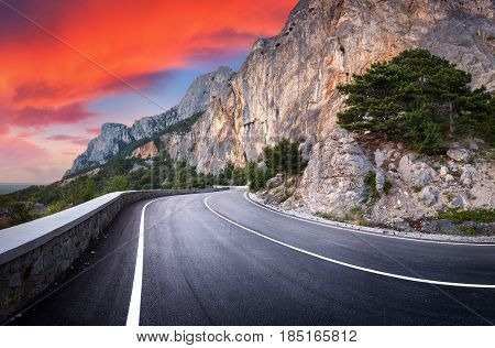 Asphalt road. Landscape with beautiful winding mountain road with a perfect asphalt, high rocks, trees, amazing sky with red clouds at sunset in summer. Panoramic. Travel background. Mountain highway