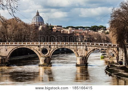 Sisto Bridge and the dome of Saint Peter. Rome Italy. Rome's historic center. Detail of a famous bridge in the Trastevere area in Rome. Basilica of Saint Peter and the Tiber River. Cloudy sky