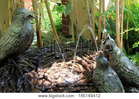 Pretty little bird bath with image of nest and three birds spouting  water towards each other,