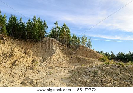 Nature background of kaolin quarry,Kyshtym, Southern Urals, Russia. Kaolin slope with summer trees -nature background with pine trees on the kaolin hill. Summer nature with kaolin slope and forest summer trees