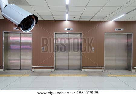 cctv security camera with closed metal office building elevator doors in modern building security technology concept.
