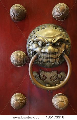 A brass door knocker on the red door of a Chinese temple