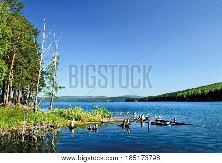 Summer water landscape - coast of St Faith Island at Turgoyak Lake, Southern Urals, Russia. Colorful summer landscape with water and mountains. Lake waters in summer sunny day -summer landscape view. Summer water background