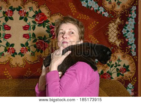 Close-up half length portrait of elderly lady in bright magenta blouse that is holding on her shoulder the black cat on handmade print carpet background.