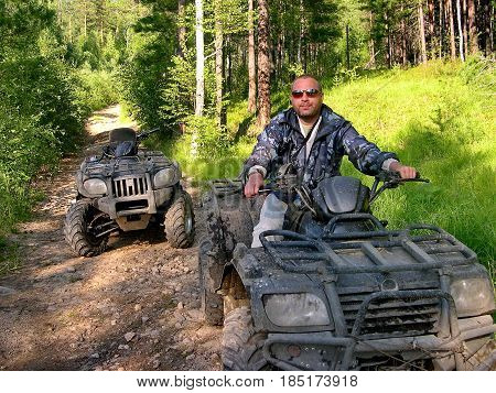 Lake Baikal, Russia - July 29, 2016: The man on ATV is riding off road the taiga