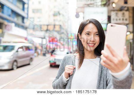 Woman taking selfie by mobile phone in Mongkok city