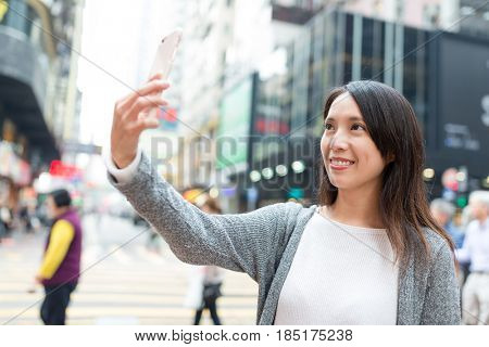 Young woman take selfie by mobile pone in Hong Kong