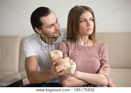 Guilty boyfriend asking for forgiveness, presenting offended girlfriend a teddy bear toy, lady looking proud sitting with arms crossed not going to take gift. Reclaim a fault, apology not accepted