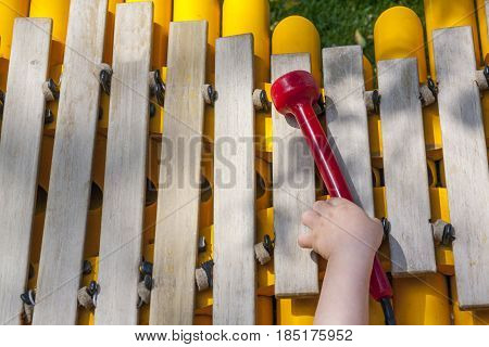 Baby boy playing take the mallet of wooden xylophone. He is at playground