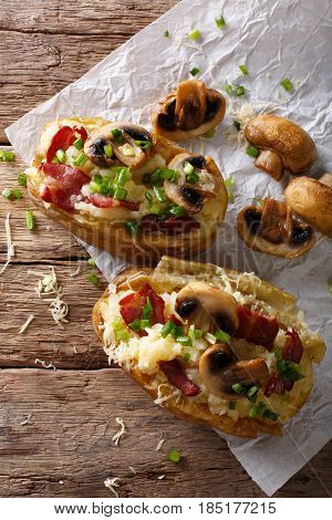 Hearty Hot Baked Potatoes With Bacon, Mushrooms, Onions And Cheese Close-up. Vertical Top View