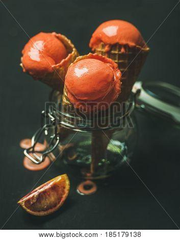 Refreshing summer blood orange ice cream or sorbet scoops in sweet waffle cones in glass jar, dark background, selective focus