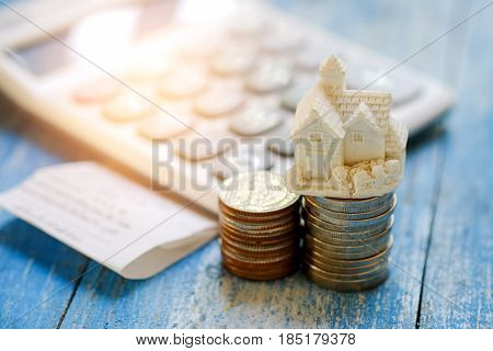 House savings concept,House model and coins with calculator and slip on blue wooden.