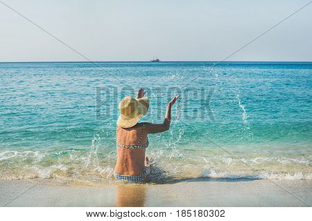 Beautiful slim senior woman tourist in bikini sitting on sand enjoying sea at Meditteranean resort of Turkey in Alanya, Kleopatra beach