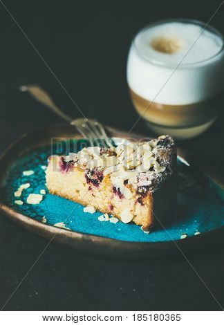 Dessert and coffee. Piece of lemon, ricotta, almond and raspberry gluten-free cake and glass of latte over dark wooden background, selective focus, vertical composition
