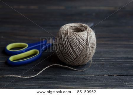 Pair of scissors and spool ball of twine string on a rustic dark table as background