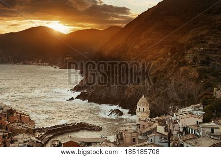 Colorful sunset in Vernazza with buildings on rocks over sea in Cinque Terre, Italy.