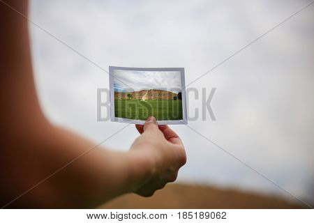 a young girl holding an instant photo in front of a landscape that is the same but a close up instead of a wide angle