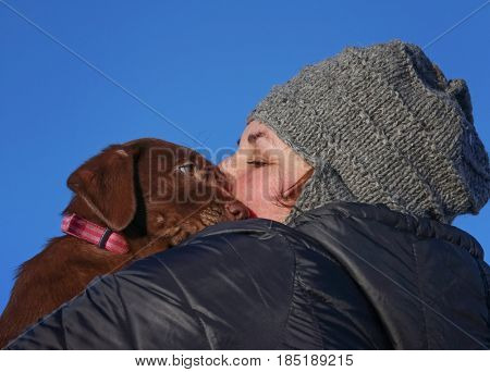 a chocolate lab puppy and her owner cuddling on a cold winter day