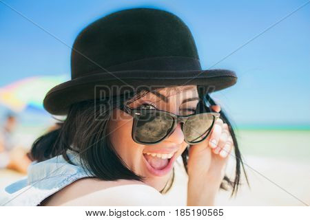 Close up portrait of a woman in blue shirt , sunglasses and summer black bowler trendy hat. Beauty cute girl on a tropical beach sea ocean shore with large stones. Outdoor summer lifestyle.