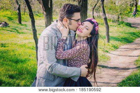 Beautiful couple standing in the spring park and hugging each other. Woman in flower wreath in long hair.