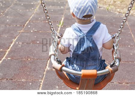 2 year-old boy playing on adapted swing. Playground toy