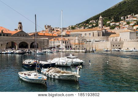 Small boats bobbling along the water in Dubrovnik's old harbour.