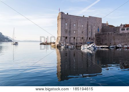 The imposing structure of St John's Fortress located at the entrance of Dubrovnik's port - captured over the still waters early one morning.